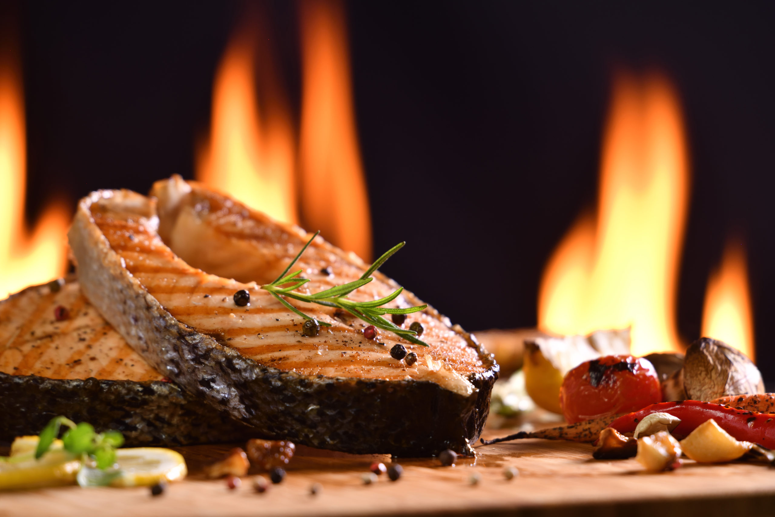 Grilled salmon fish and various vegetables on wooden table background